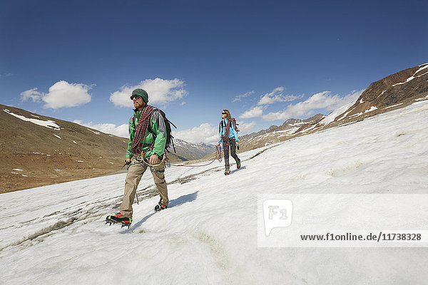 Young couple hiking down ice on Val Senales Glacier  Val Senales  South Tyrol  Italy