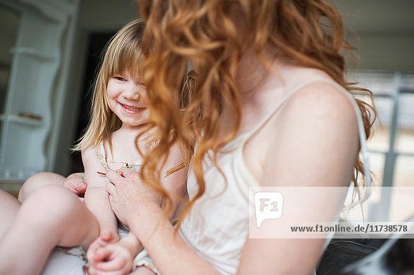 Mother tickling daughter
