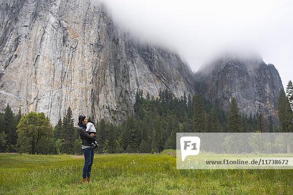 Mittelgrosse erwachsene Frau mit Kleinkind-Tochter auf einer Wiese  Yosemite National Park  Kalifornien  USA