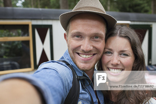 Happy couple taking selfie on cabin porch