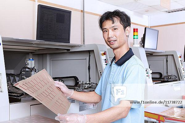 Young man holding sheet of flexible circuits  looking at camera smiling