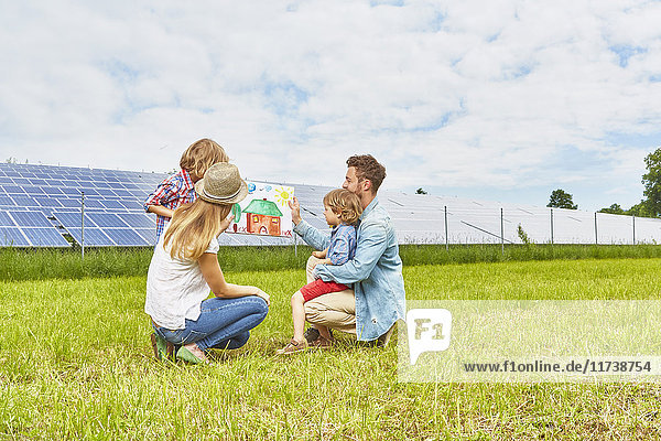 Junge Familie sitzt auf dem Feld und schaut auf eine Kinderzeichnung von einem Haus neben einem Solarpark