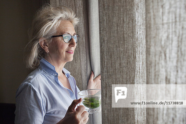 Senior woman holding drink  looking out of window