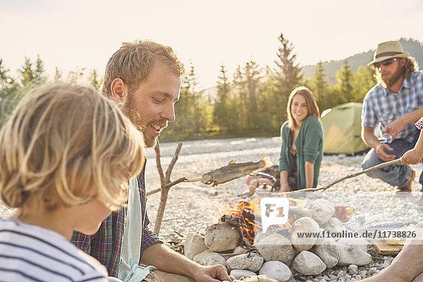 Familie sitzt am Lagerfeuer und kocht Fisch an einem Ast