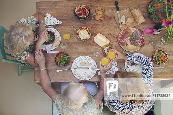 Three women having lunch together at home  overhead view