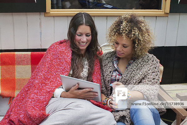 Two female friends using digital tablet on cabin porch