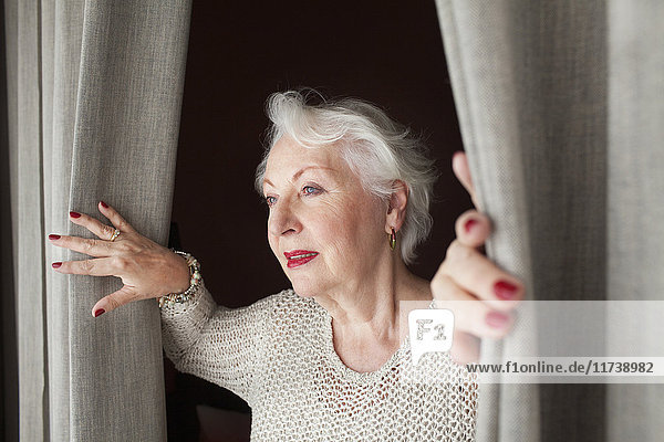 Senior woman  opening curtains