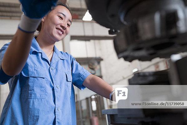 Niedrigwinkelaufnahme einer Fabrikarbeiterin bei der Arbeit an einer Maschine in einer Kranfabrik  China