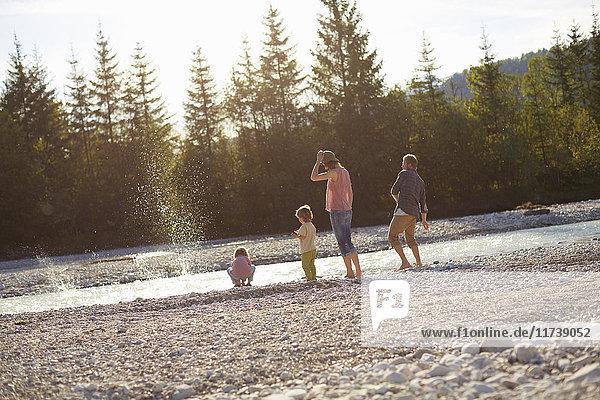 Rückansicht von Familien-Abschöpfsteinen am Fluss