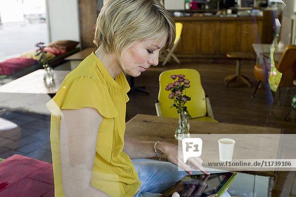 Mid adult woman using digital tablet in cafe