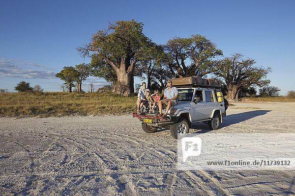 Ehepaar mit Söhnen auf Fahrzeug  Nxai-Pan-Nationalpark  Kalahari-Wüste  Afrika