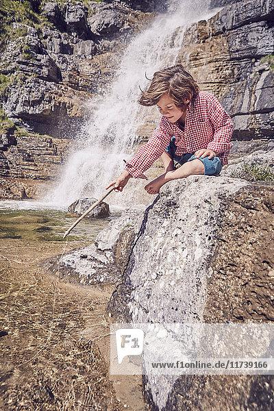Junge sitzen auf einem Felsen neben einem Wasserfall  halten einen Stock und schauen ins Wasser