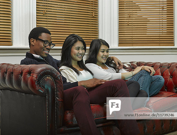 Three young adult friends sitting on sofa together