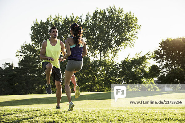 Young man and woman doing running on spot training in park