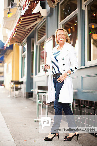 Mature woman in white coat and jeans  smiling