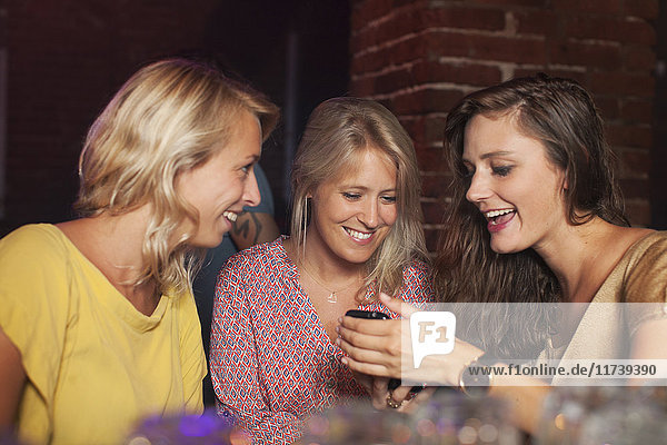 Young women smiling at smartphone in club