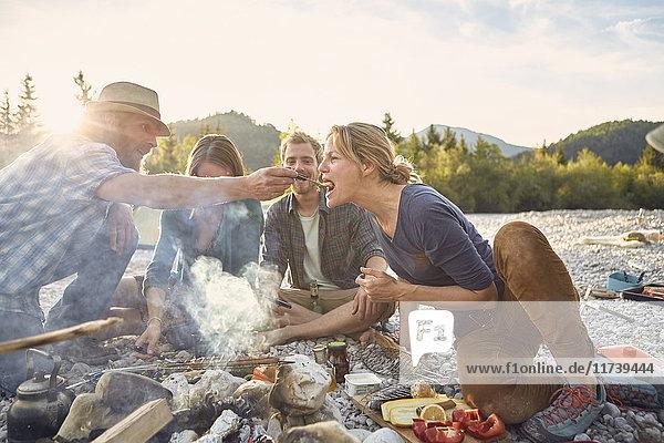 Mittelgroßer erwachsener Mann  der eine reife Frau am Lagerfeuer füttert