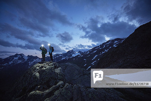 Young hiking couple looking out over rugged mountains at night  Val Senales Glacier  Val Senales  South Tyrol  Italy