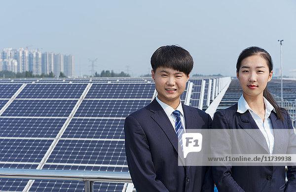 Geschäftsmann und Geschäftsfrau auf dem Dach einer Solarmodul-Montagefabrik  Solar Valley  Dezhou  China