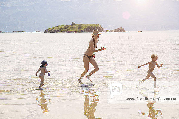 Mature woman running in sea with two sons  Lopar  Rab Island  Croatia