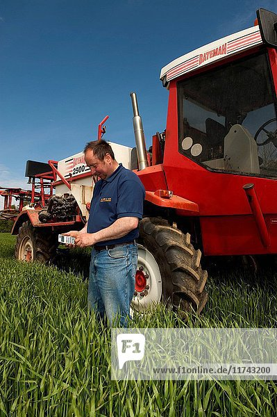 Farmer standing in front of a Bateman sprayer using a calculater to work out spryaing rates. (Photo by: Wayne Hutchinson/Farm Images/UIG)