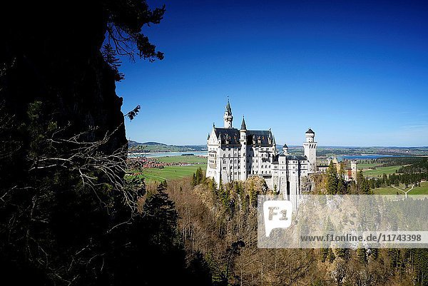 Germany  Bavaria  Romantic Road (Romantische Strasse)  Schwangau  Neuschwanstein Castle  19th-century Romanesque Revival palace commissioned by Ludwig II of Bavaria located on a rugged hill above the village of Hohenschwangau near Füssen  view from Marienbrücke (Queen Mary's Bridge)