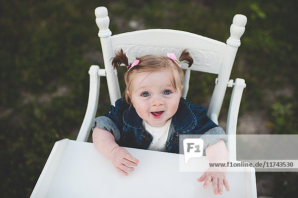 Portrait of baby girl in high chair