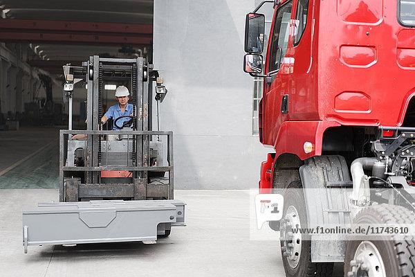 Männlicher Fabrikarbeiter fährt Gabelstapler in Kranfabrik  China