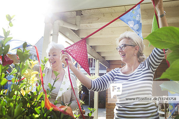 Two women in garden  hanging colourful bunting