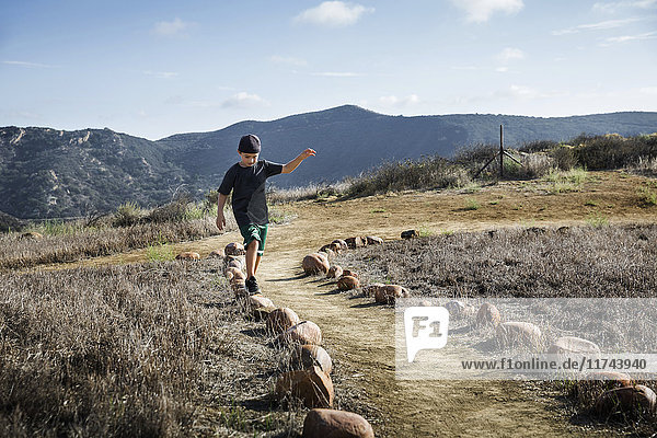 Boy stepping across row of footpath stones  Thousand Oaks  California USA