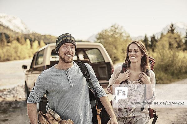 Junges Paar bereitet sich zum Wandern vor  trägt Brennholz  lächelt