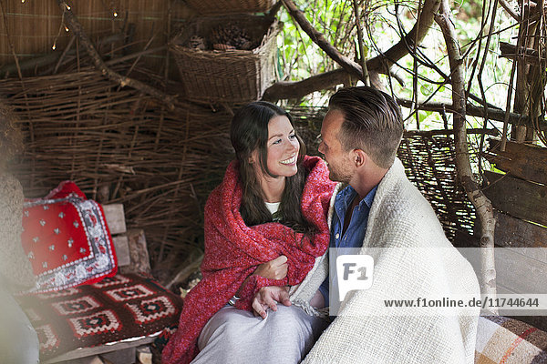 Romantic couple wrapped in blankets in cabin