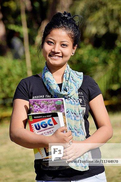 Beautiful young girl-student holding textbooks outside in the garden  Pune  Maharashtra.