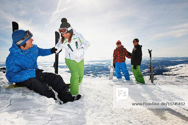 Snowboarder und Skifahrer auf dem Gipfel des Berges mit Ausrüstung