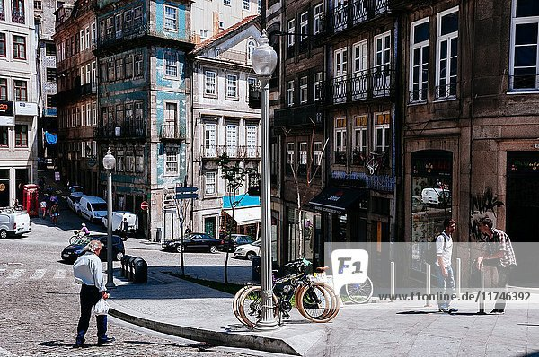 People walking on a cobbled street among old and decadent buildings  Porto  Portugal.