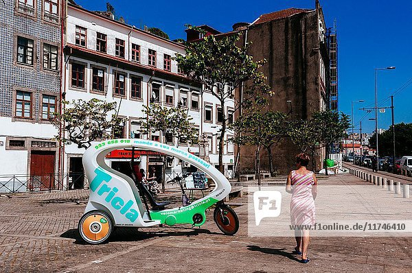 Woman walking by Tricla tours ecological tricycle parked in front of tipical old decadent buildings  Porto  Portugal.