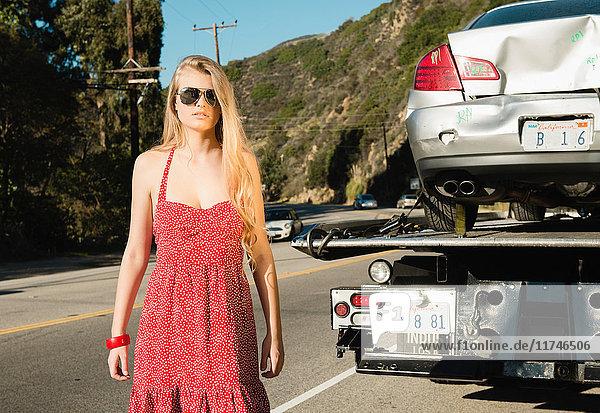 Junge Frau schaut in die Kamera  als ein Abschleppwagen ein beschädigtes Auto wegbringt