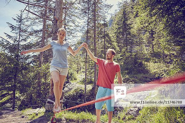 Frau balanciert mit Hilfe eines Mannes auf einem Seil  Ehrwald  Tirol  Österreich