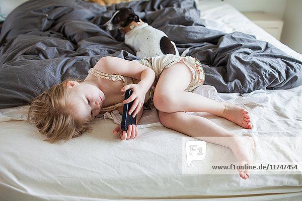 Girl lying on bed using smartphone