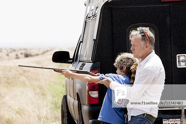 Vater unterrichtet Sohn mit Gewehr  Texas  USA