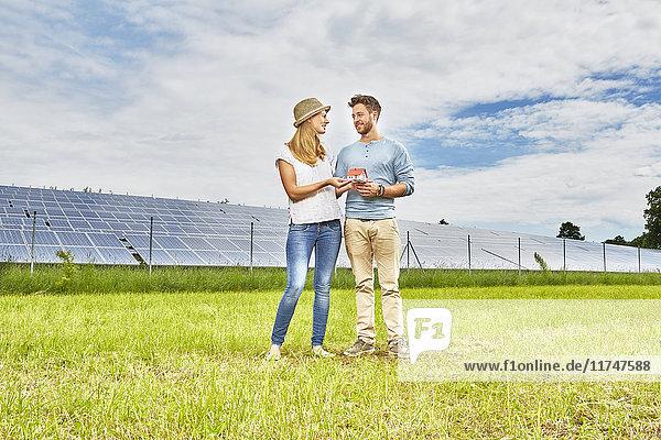 Junges Paar steht auf dem Feld und hält ein kleines Modell eines Hauses neben einem Solarpark