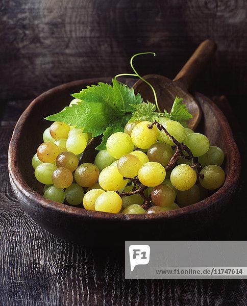 Traube mit grünen Trauben in einer alten Holzschale