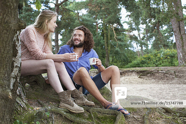 Junges Paar beim Plaudern am Baum