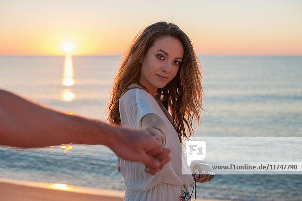 Junge Frau hält ihrem Freund bei Sonnenuntergang am Strand die Hand  Kastilien  Sardinien  Italien
