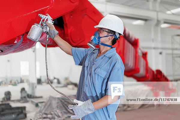 Männlicher Arbeiter sprüht einen Kranarm in einer Fabrikhalle rot an  China