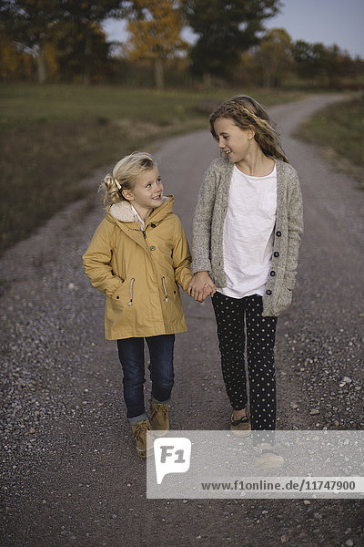 Two young girls walking along country road  hand in hand