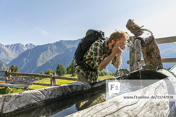 Young male hiker washing face in rustic trough  Karthaus  Val Senales  South Tyrol  Italy