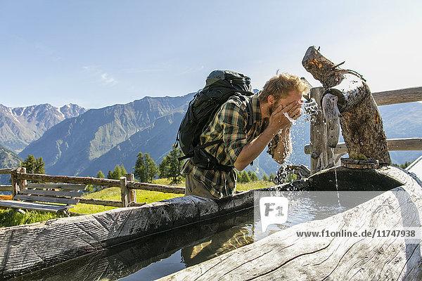 Junger männlicher Wanderer wäscht Gesicht in rustikalem Trog  Karthaus  Schnalstal  Südtirol  Italien