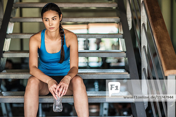 Young woman sitting on stairs with water bottle