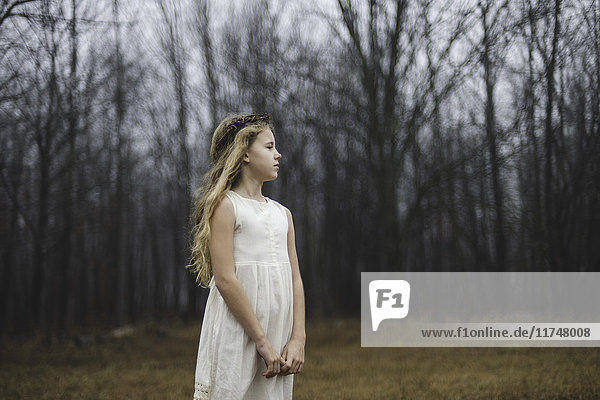 Portrait of long blond haired girl looking away in forest field